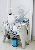 Runner of woven paper strips as centrepiece of shabby chic still-life with old metal watering can and vintage stool