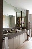 Huge mirror in modern bathroom with two sunken sinks in stone washstand