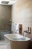 Free-standing bathtub in modern bathroom with gleaming waterfall tap fitting and bathtub rack; shower area behind glass partition in background