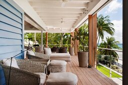 Roofed balcony with comfortable seating and view of palm trees and beach