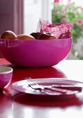 Cheerful mixture of colours - pink plastic bowl of apples and blurred, matching place setting in foreground on red table