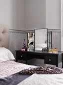 Dressing table next to bed in bedroom