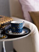 Cup and saucer and books on side table in living room