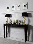 Lamps, vases and animal figurines on console table