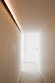 Minimalistischer Gang mit indirektem Licht an Wand