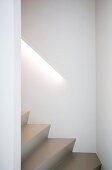 Hellgraue Stufen einer gewendelten Treppe mit Handlauf und integrierter Beleuchtung