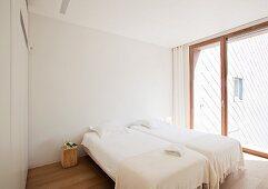 Helles modernes Schlafzimmer mit Fensterfront