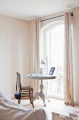Helle Zimmerecke mit antikem, weiss lackierten Tisch vor Fenstertür; daneben ein Vintage-Binsenstuhl
