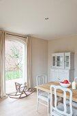 Esszimmer im Landhausstil mit hellem Holztisch und weissen Vintage-Stühlen; im Hintergrund ein weisses Esszimmerbuffet und ein antiker Kinder-Schaukelstuhl