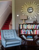 Blue armchair next to half-height bookcase below mirror with sunburst gilt frame on wall