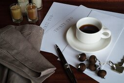 Writing paper and ball-point pen next to cup of coffee on table