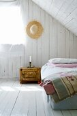 Simple attic bedroom with white-painted boards on walls and floor