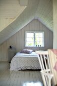 White, wood-clad attic bedroom in simple wooden house