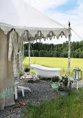 Bathtub on gravel in front of Oriental-style tent and view of landscape