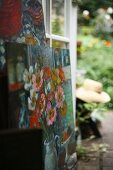 Floral oil paintings stacked in front of open terrace door with view of garden