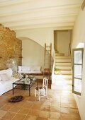 Simple, Mediterranean interior with terracotta tiles and masonry staircase