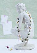 weiße Keramikfigur mit umgehängtem Schlüssel und Kette aus Gänseblümchen