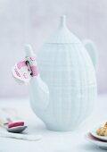 Stoff mit Gänseblümchen-Motiv als Tropfenfänger auf weisser Porzellankanne