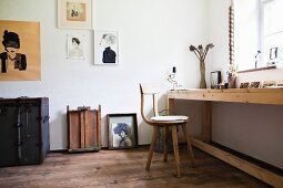 Long wooden table and wooden chair below window, modern portraits on wall in room with wooden floor