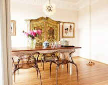 Dining table, postmodern plexiglass chairs and antique-effect cupboard