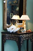 Gilt-framed mirror on wall and collectors' items on ornate, lacquered table