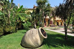 Extensive Mediterranean gardens; large amphora lying at an angle in foreground