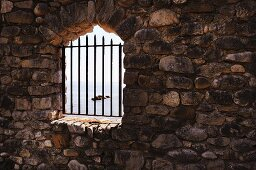 Barred, arched window opening in stone wall
