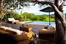 Rattan furniture on wooden terrace with adjacent infinity pool and wide view of landscape