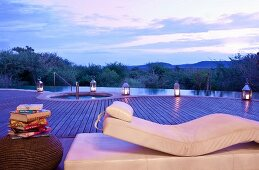 Luxurious relaxation couch in front of infinity pool beneath boundless evening sky