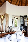 Airy interior with curved walls, rustic roof structure, narrow windows and tree-trunk columns