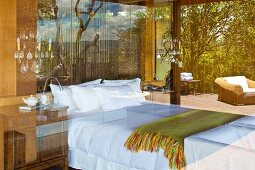 Bedroom and sun terrace viewed through a glass wall