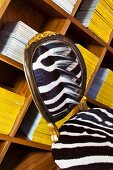 Original chair with zebra skin upholstery in front of books stacked on wooden shelves