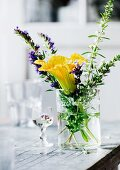 Yellow courgette flower and flowering herbs in glass of water on old table