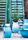 Old blue enamel jugs on gravel in front of peeling shutters