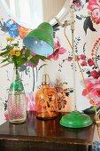 Lamp and bottles on bedside table against floral wallpaper