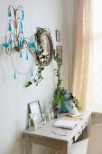 Small console table with drawers below sconce and framed portrait