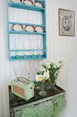 Retro radio on metal cabinet below turquoise plate rack
