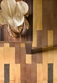 Chrome decorative vase on strongly grained wooden table on multicoloured parquet flooring