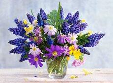 Spring posy of grape hyacinths, anemones and primulas