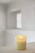 Cream candle in blurred, white, daylight interior with arched casement window in background (Schloss Schauenstein)