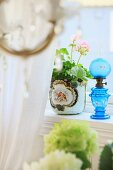 Blue glass oil lamp next to potted geranium on windowsill