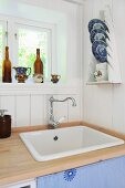 Kitchen sink and blue and white china plates in plate rack on white wooden wall