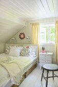 Airy bedroom with wicker under-bed drawers and cheerful embroidered scatter cushions