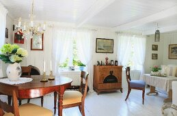 Open-plan interior with antique dining table and chairs below chandelier in living-dining area