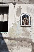 Religious figurines in small niche of weathered facade