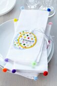 White linen napkins decorated with colourful miniature pompoms & name tags