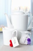Milk jugs decorated with labels & pompoms