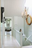 White-painted landing with gilt-framed mirror and chandelier