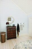 Antique chest of drawers and round mirror in wood-clad, attic bedroom