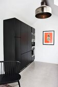 Black kitchen cabinet with fitted appliances and industrial-style, metal pendant lamps